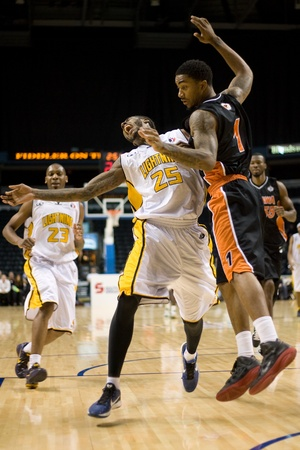 London Ontario, Canada - December 10, 2011. Gabe Freeman (25) is fouled by Marcus Johnson (1) in a National Basketball League of Canada game between the Oshawa Power and the London Lightning. The visiting Oshawa Power handed London their third loss of the