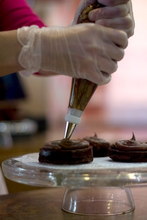 London Ontario, Canada - April 2, 2012. With Easter fast approaching bakeries are quickly preparing for the increase in demand of all things sweet.  Becky Brown, 38, of Sweet Cakes finishes icing chocolate peanut butter brownies.  Brown says that Easter w