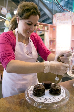 London Ontario, Canada - April 2, 2012. Becky Brown, 38, of Sweet Cakes finishes icing chocolate peanut butter brownies.  Brown says that Easter week is the busiest week of the year, for the company and that it even surpasses Valentines Day as it is a s