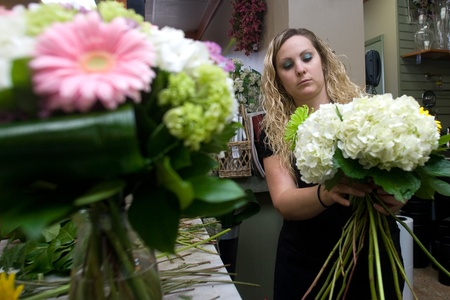 London Ontario, Canada - April 3, 2012.  Lauren Schell, 27, prepares a bouquet of flowers for sale inside Boxwoods. Owned by David Friesen, 49, Bowood's is located on Richmond Row.  As a florist Friesen and his staff will often spend between four to six h Stock Photo - 13022734
