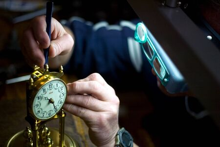 London Ontario, Canada - April 4, 2012.  Working at the same desk that his father did, Tom Buchenthal repairs the movement of a anniversary clock. Oxford Clock Shop was opened in 1954 by Toms father Hans Buchenthal. The shop has been in the same location