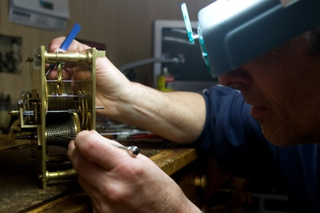 London Ontario, Canada - April 4, 2012.  Working at the same desk that his father did, Tom Buchenthal repairs the movement for a clock. Oxford Clock Shop was opened in 1954 by Tom's father Hans Buchenthal. The shop has been in the same location on Oxford  Stock Photo - 13073017