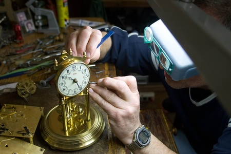 London Ontario, Canada - April 4, 2012.  Working at the same desk that his father did, Tom Buchenthal repairs the movement inside an anniversary clock. Oxford Clock Shop was opened in 1954 by Tom's father Hans Buchenthal. The shop has been in the same loc Stock Photo - 13073034