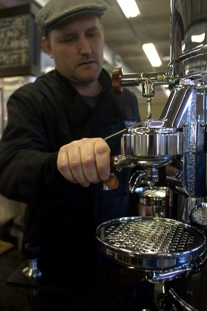 London Ontario, Canada - April 5, 2012. David Cook, owner of Habitual Chocolate prepares an expresso on an Italian Elecktra Expresso maker. 新聞圖片