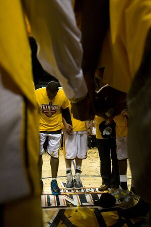 London Ontario, Canada - March 25, 2012. Members of the London Lightning gather at centre court for a team prayer.  The London Lightning defeated the Halifax Rainmen 116-92 in the fifth and deciding game to win the National Basketball League of Canadas c
