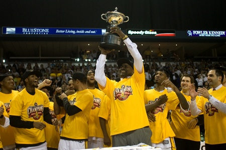 hoists: London Ontario, Canada - March 25, 2012. London Lightning coach and NBL Coach of the Year Michael Ray Richardson hoists the leagues championship trophy. The London Lightning defeated the Halifax Rainmen 116-92 in the fifth and deciding game to win the Nat
