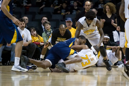 london lightning: London Ontario, Canada - March 9, 2012. Tim Ellis (23) of the London Lightning wrestles for the ball against a Saint John Mill Rats player while London Lightning Eddie Smith yells from the sidelines in game two of their best of three first round, the Ligt Editorial