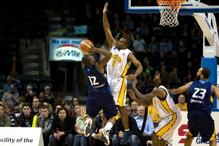 playoffs: London Ontario, Canada - March 9, 2012. Brandon Dean (11) of the London Lightning defends against Anthony Anderson of the Saint John Mill Rates. The Ligthning won the first round of the playoffs defeating the Saint John Mill Rats 87-82 in front of a recor Editorial
