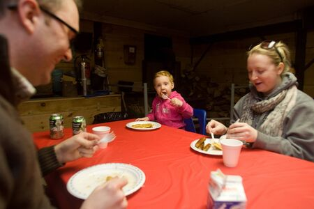 Thorndale Ontario, Canada - March 3, 2012. Jordyn Donkervoort, middle along her mom Sara Donkervoort and father Jason Shaw enjoy the real reason why families trek to the Kinsmen Fanshaw Sugar Bush, the pancakes.  The three were warming up after their tour Stock Photo - 13073161