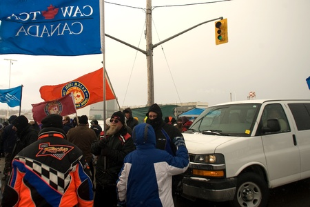 London Ontario, Canada - January 2, 2012. Canadian Auto Workers locked out from the Electro Motive factory in London block a van suspected of carrying replacement workers from entering the factory. CAW Local 27 workers were locked out from the Electro Mot 新聞圖片
