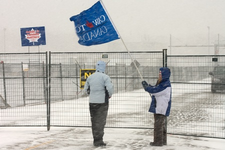 London Ontario, Canada - January 2, 2012. Two Canadian Auto Workers locked out from the Electro Motive factory in London inspect a temporary fence erected by the company. CAW Local 27 workers were locked out from the Electro Motive Diesel factory in Londo 新聞圖片