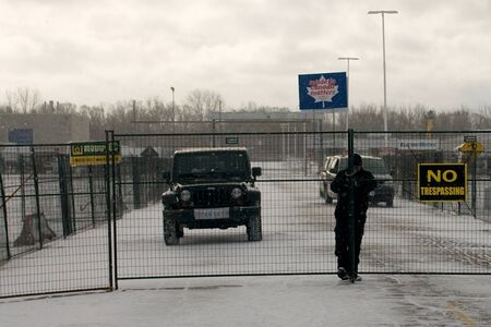 London Ontario, Canada - January 2, 2012. A security guard locks a chain around a temporary fence installed around the Electro Motive factory.  CAW Local 27 workers were locked out from the Electro Motive Diesel factory in London on January 1, 2012 after