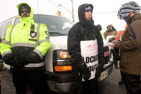 London Ontario, Canada - January 2, 2012. Locked out Canadian Auto Worker union members block a van carrying suspected replacement workers from entering the Electro Motive factory. CAW Local 27 workers were locked out from the Electro Motive Diesel factor