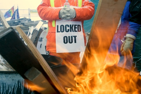 London Ontario, Canada - January 2, 2012. Locked out Canadian Auto Worker union members gather around a fire to keep warm as they walk a picket line in front of the Electro Motive plant.  CAW Local 27 workers were locked out from the Electro Motive Diesel
