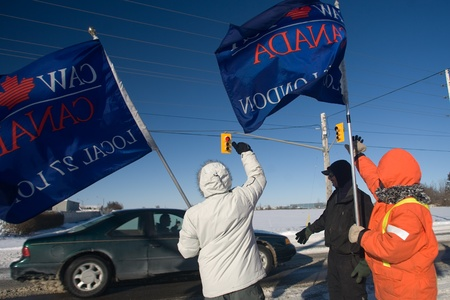 London Ontario, Canada - January 3, 2012. Locked out workers from the Electro Motive factory in London wave to passing motorists as they walk a picket line in front of the factory. The workers have been receiving a
