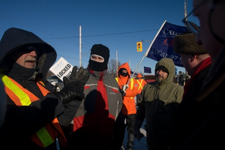 London Ontario, Canada - January 3, 2012. City of London Council members Dale Henderson, right and Stephen Orser second from right listen to workers who are locket out at the Electro Motive factory in London.  Nearly 700 union and non union members were l Redakční