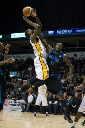 halifax rainmen: London Ontario, Canada - January 19, 2012. Gabe Freeman (25) of the London Lightning goes up for a basket against and is fouled by Tyrone Levett (32) of the Halifax Rainmen in a regular season National Basketball League of Canada game between the first pl