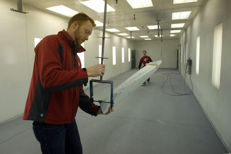 London Ontario, Canada - March 5, 2012. Andrew Jago, left and Steve Mann load a single shell into the paint booth to be painted. Hudson Boat Works has been building high performance racing shells since 1981. Located in London Ontario, Canada the company s Stock Photo - 13073153