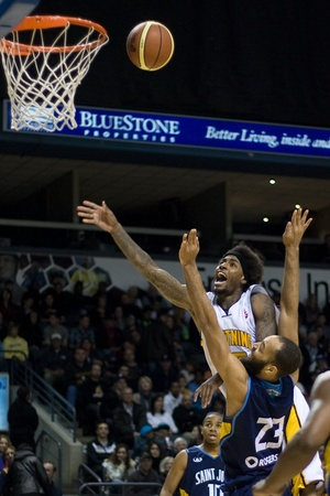john labatt centre: London Ontario, Canada - March 9, 2012. Gabe Freeman (white shirt) of the London Lightning follows his shot as he drives past Kevin Francis (23) of the Saint John Mill Rats in game two of their best of three first round, the Ligthning won the first round  Editorial