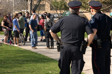 occupy london: London Ontario, Canada - March 21, 2012. Members of Occupy London hold a press conference in Victoria Park under the watchful eye of London Police. The group read a prepared statement regarding the Ontario Ombudsmans report that finds London  City Council
