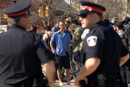 London Ontario, Canada - March 21, 2012. Eric Sheppard (blue shirt) and other members of Occupy London hold a press conference in Victoria Park under the watchful eye of London Police. The group read a prepared statement regarding the Ontario Ombudsmans r Stock Photo - 13073123