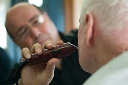 hair clippers: London Ontario, Canada - March 28, 2012. Vincenzo Ioele owner of Vinces Barber Shop at 780 Dundas Street in London trims the beard of George Stovel a regular customer. Ioele opened the shop in 1980 and has been in the same location since then. He has a