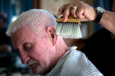 London Ontario, Canada - March 28, 2012. Vincenzo Ioele owner of Vinces Barber Shop at 780 Dundas Street in London brushes away clippings from the neck of George Stovel a regular customer. Ioele opened the shop in 1980 and has been in the same location