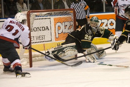 john labatt centre: London Ontario, Canada - January 27, 2012. London goalie Michael Houser - without his stick - makes a save against Zack MacQueen (21) of the Windsor Spitfires in a regular season Ontario Hockey League game between the London Knights and the Windsor Spitfi Editorial