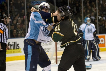London Ontario, Canada - February 4, 2012. Trevor Carrick of the Majors (4) and Tyler Ferry (21) of the Knights fight it out in a Ontario Hockey League game between the London Knights and the Mississauga St. Michaels Majors. London won the game 5-2.  Stock Photo - 13140537