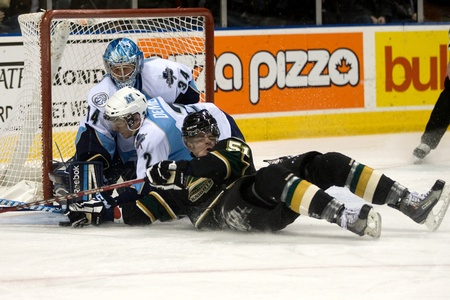 London Ontario, Canada - February 4, 2012. London Knight Austin Watson (51) and Dylan Demelo slide into Major goalie Brandon Maxwell in a Ontario Hockey League game between the London Knights and the Mississauga St. Michaels Majors. London won the game 5- Stock Photo - 13140551