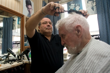 clippers comb: London Ontario, Canada - March 28, 2012. Vincenzo Ioele owner of Vinces Barber Shop at 780 Dundas Street in London cuts the hair of George Stovel a regular customer. Ioele opened the shop in 1980 and has been in the same location since then. He has a r Editorial