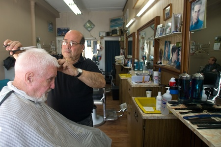 London Ontario, Canada - March 28, 2012. Vincenzo Ioele owner of Vinces Barber Shop at 780 Dundas Street in London cuts the hair of George Stovel a regular customer. Ioele opened the shop in 1980 and has been in the same location since then. He has a r