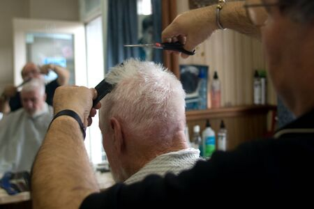 London Ontario, Canada - March 28, 2012. Vincenzo Ioele owner of 'Vince's Barber Shop' at 780 Dundas Street in London cuts the hair of George Stovel a regular customer. Ioele opened the shop in 1980 and has been in the same location since then. He has a r