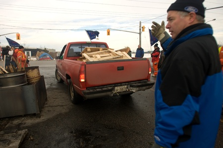 skids: London Ontario, Canada - January 6, 2012. A worker directs a truck loaded with wooden skids that will be used for firewood. Locked out Electro Motive workers picket in front of the factory in London. Electro Motive workers were locked out by the parent co Editorial