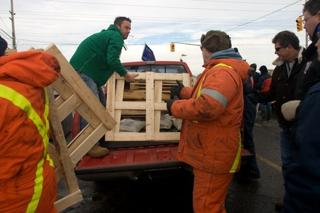 skids: London Ontario, Canada - January 6, 2012. Locked out Electro Motive workers unload wooden skids that will be used for firewood. Electro Motive workers were locked out by the parent company - Caterpillar- on January 1, 2012 after the union rejected the com Editorial