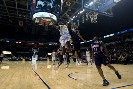 john labatt centre: London Ontario, Canada - January 6, 2012. Eddie Smith (20) of the London Lightning tries to block a shot by Jessan Gray (25) of the Summerside Storm in a National Baskeball League of Canada game between the London Lightning and the Summerside Storm. Londo Editorial