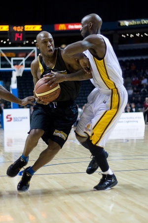 London Ontario, Canada - January 7, 2012. A Halifax Rainmen player drives around DeAnthony Bowden of the London Lightning during a National Basketball League of Canada game between the London Lightning and the Halifax Rainmen. The Rainmen were forced to w Stock Photo - 13118972