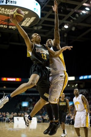 london lightning: London Ontario, Canada - January 7, 2012. Joey Haywood (13) of the Halifax Rainmen goes up for a shot while Gabe Freeman of the London Lightning does his best to defend during a National Basketball League of Canada game between the London Lightning and th