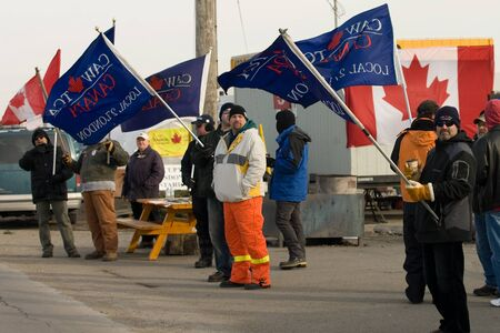 London Ontario, Canada - January 9, 2012. Locked out Electro Motive workers walk the picket line in front of the factory located in London. The company, owned by Caterpillar locked out more than 700 union and non-union workers on January 1, 2012 at the Ca Stock Photo - 13118969