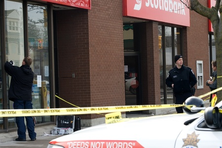 London Ontario, Canada - January 11, 2012. Two police officers outside the Scotiabank at Richmond and Oxford Streets that was one of four banks to be robbed in quick succession. The suspect is believed to have fled in a grey Jeep that was involved in a mo Stock Photo - 13140738