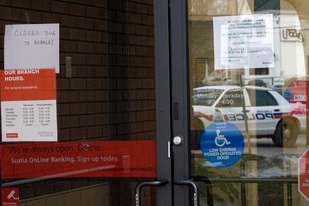 beroofd: London Ontario, Canada - 11 januari 2012. De reflectie van een London Police Crusier en mededelingen op de deur vertellen het verhaal aan de Scotiabank op de hoek van Richmond en Oxford Street. De bank is een van de vier die werd beroofd in snel tempo op. De su