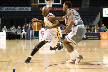 London Ontario, Canada - January 12, 2012. DeAnthony Bowden (white jersey) carries the ball up court as Akeem Wright defends in a regular season National Basketball League game between the London Lightning and Moncton Miracles. London won the game 124 -11 Editorial