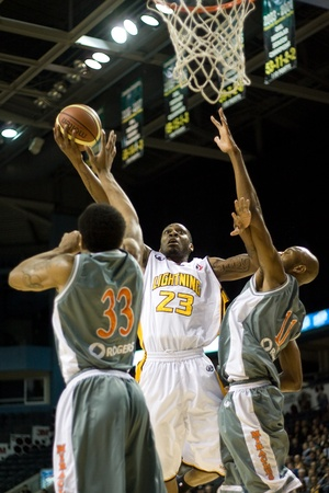 London Ontario, Canada - January 12, 2012. Tim Ellis (23) of the London Lightning goes up for a shot against George Fudge (33) and Trayvon Lathan (11) in a regular season National Basketball League game between the London Lightning and Moncton Miracles. L