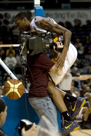 London Ontario, Canada - January 12, 2012. Tim Ellis of the London Lightning tries to avoid the TV cameraman in a regular season National Basketball League game between the London Lightning and Moncton Miracles. London won the game 124 -113 extending thei