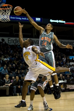 London Ontario, Canada - January 12, 2012. Brandon Dean (11) of the London Lightning is fouled by Darrell Wonge (14) in a regular season National Basketball League game between the London Lightning and Moncton Miracles. London won the game 124 -113 extend