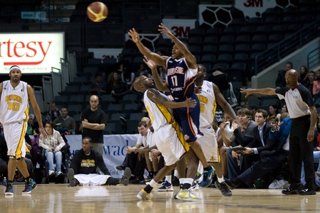 London Ontario, Canada - January 6, 2012. Stephen McDowell (11) makes a pass past Eddie Smith (20) of the London Lightning in a National Baskeball League of Canada game between the London Lightning and the Summerside Storm. London won the game 106-98.