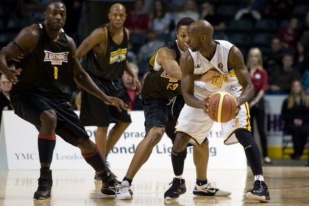 London Ontario, Canada - January 7, 2012. DeAnthony Bowden, white jersey, of the London Lightning looks to make a pass during a National Basketball League of Canada game between the London Lightning and the Halifax Rainmen. The Rainmen were forced to wear Editorial
