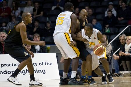 London Ontario, Canada - January 7, 2012. Brandon Dean, right of the London Lightning moves around opposition and his own player during a National Basketball League of Canada game between the London Lightning and the Halifax Rainmen. The Rainmen were forc