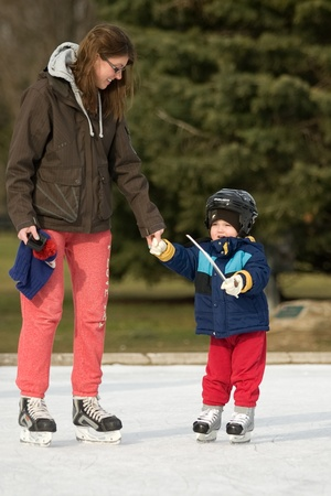 London Ontario, Canada - January 9, 2012. Testing out the new skates. Two year old Bentley Michalak tries out skates he was given at Christmas along with his mother, Karolina Michalak. The two were enjoying unseasonably warm temperatures and bright sun as Stock Photo - 13118926