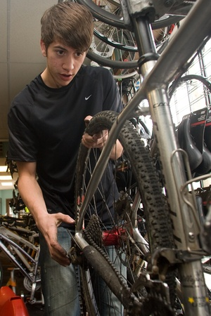 London Ontario, Canada - April 12, 2012. Graham Woods works on a servicing a bike as part of a spring tune up at Village Cycle in the Old South region of London Ontario. The company that has been in business for five years sells everything from entry leve 新聞圖片